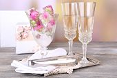 Ice cubes with rose flowers in glass bowl and two glasses with champagne on wooden table, on bright