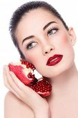 Portrait of young beautiful woman with pomegranates in her hand over white background
