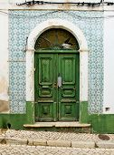 Antique Door In A House With Worn Tiles Wall.