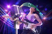 Pretty girl playing guitar against digitally generated music symbol design