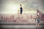 Young businesswoman pulling a tightrope for business woman against balcony overlooking city