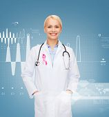 healthcare and medicine concept - smiling female doctor with stethoscope and pink cancer awareness r