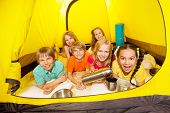 Six funny children laying in the tent