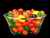 stock photo of jelly beans  - Fruit jelly beans in many colors in a glass bowl on a black background - JPG