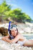 Pretty, young woman on a beach during her summer vacation with snorkel lying on beach with snorkelin