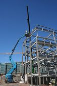 foto of cherry-picker  - Cherry picker and crane beside metal frame of new building - JPG