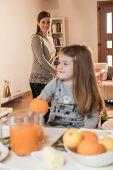 Little girl having breakfast, mother in the background