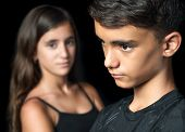 Sad young teen couple - boy and girl - on a black background