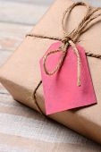 Closeup of a plain wrapped Christmas Present with a red gift tag. The tag is blank. Shallow Depth of
