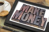 make money online concept - words in vintage letterpress wood type on a digital tablet with a cup of coffee