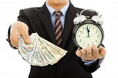 picture of holding money  - businessman holding money and clock. time is money concept