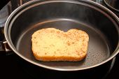 A Slice of Raw French Toast Cooking In A Fry Pan