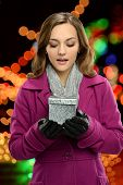 Portrait of young woman holding gift bow with holiday lights in background