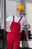 foto of crane hook  - Young builder standing near to chain with crane hook - JPG