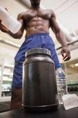 Shirtless body builder scooping up protein powder in gym