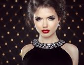 Makeup. Elegant Woman. Jewelry And Hairstyle. Attractive Lady Over Lights Background