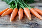 Some Fresh Carrots On Old Wooden Desk
