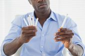 Businessman deciding between electronic or normal cigarettes in his office