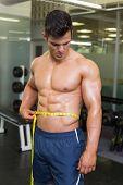 Shirtless muscular man measuring waist in gym