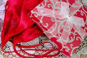 stock photo of nighties  - Sexy red lingerie with gift box on white lace background - JPG