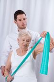 Physiotherapist Exercising With Elderly Patient