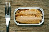 an open can of canned mackerel and a fork on a rustic wooden table