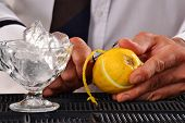 Barman peeling lemon and preparing alcoholic cocktail.