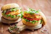 Fish and crab burgers with fresh vegetables on wooden serving boards
