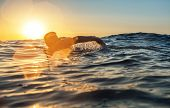 Young Man Swiming In The Sea Over Yellow Sunrise