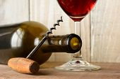 Wine still life with a bottle on its side and the bottom of a glass of red wine and a cork screw lea