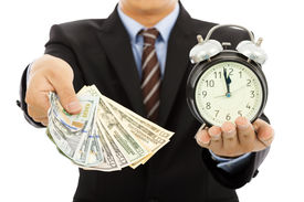 picture of money  - businessman holding money and clock. time is money concept ** Note: Shallow depth of field - JPG