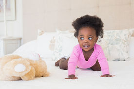 stock photo of babygro  - Baby girl in pink babygro crawling on bed at home in the bedroom - JPG