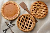 High angle shot of three fresh baked homemade pies, Apple, Cherry and Pumpkin on a burlap table cloth. Horizontal format with forks and wooden spatula.