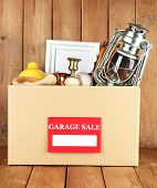 foto of yard sale  - Box of unwanted stuff ready for a garage sale on wooden background - JPG