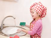 Cute Smiling Little Girl Washing The Dishes