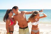 stock photo of cheating  - Teenage boy cheating girlfriend on the beach - JPG