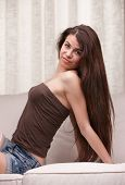 Long Hair Young Girl Posing On A Sofa