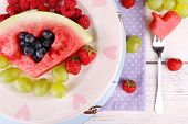 Fresh juicy watermelon slice  with cut out heart shape, filled fresh berries, on plate, on wooden background