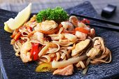 Chinese noodles with vegetables and seafood on plate on bamboo mat background