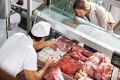 High angle view of male butcher showing meat to female customer at butchery