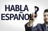 Business man pointing to transparent board with text: Do You Speak Spanish? (In Spanish)