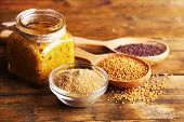 Mustard seeds, powder and sauce in glass jar, bowl and wooden spoons on wooden background