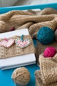 Old Notebook With Knitted Cover With Felt Heart Next To The Tangle Bright Filaments And Blanket Knit