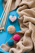 Wooden Needles Lie Next To The Bright Tangle Of Threads And Knitted Blanket On Blue Background