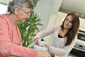 Home helper serving breakfast to elderly woman