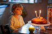 Adorable Three Year Kid Boy Celebrating Birthday And Blowing Candles