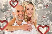Happy man giving his partner a piggy back against grey valentines heart pattern