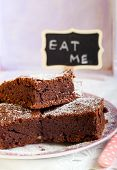 picture of eat me  - Chocolate brownies dusted with icing sugar on plate and a sign saying Eat me - JPG