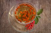 Goji Fresh Antioxidant Tea In Glass Cup And Barberries In Wooden Bowl