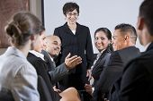 pic of motivation talk  - Diverse group of businesspeople conversing with woman standing at front - JPG